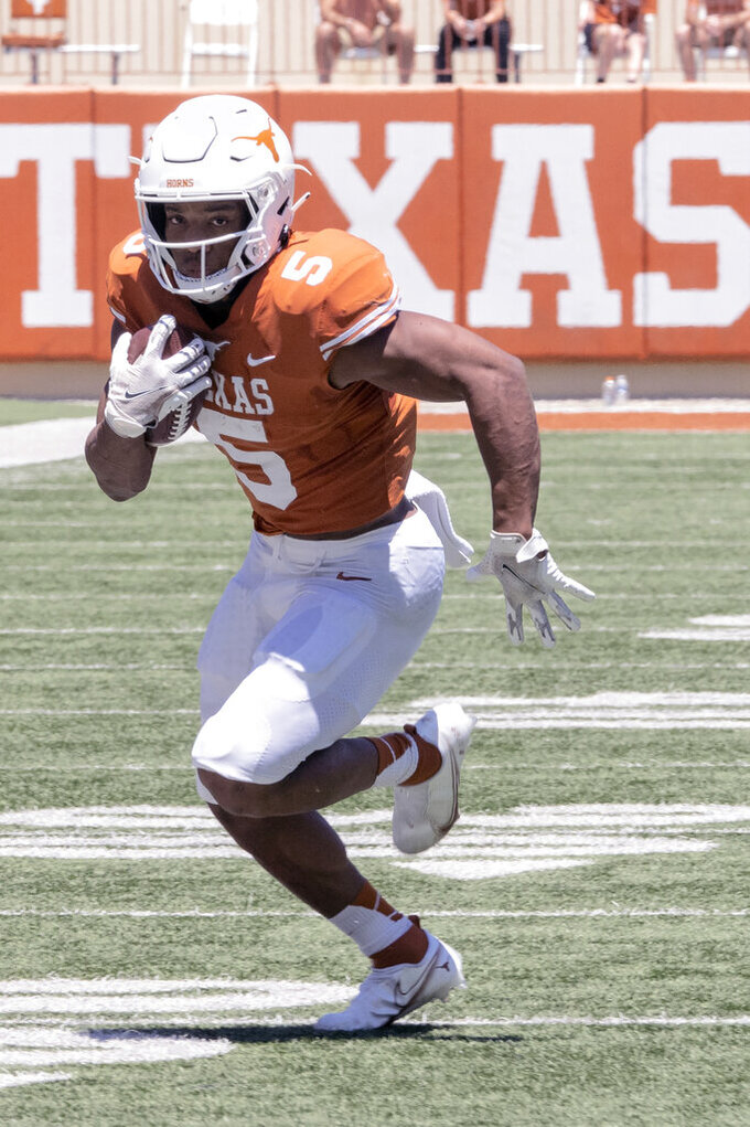 FILE - Texas running back Bijan Robinson (5) runs during the final half of the Texas Orange and White Spring Scrimmage in Austin, Texas, in this Saturday, April 24, 2021, file photo. No player frustrated Texas fans last season more than tailback Bijan Robinson. Not because of anything he did, but because of Herman's odd refusal to give him the ball more often. (AP Photo/Michael Thomas, File)