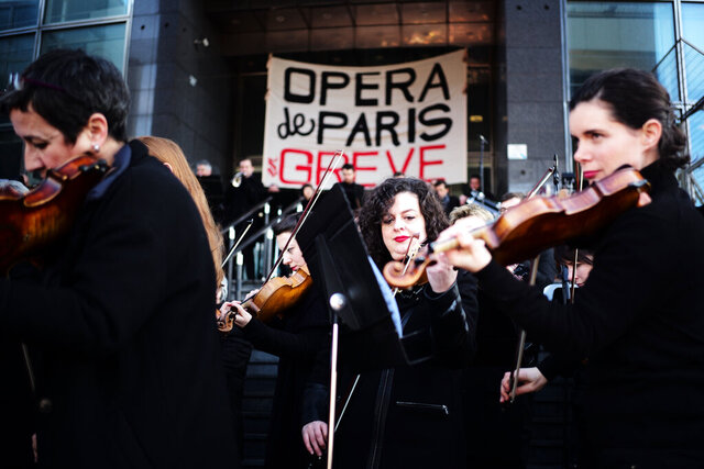 Striking musicians of the Paris Opera house perform outside the Bastille Opera house Tuesday, Dec. 31, 2019 in Paris. Banner reads : Paris Opera on strike. (AP Photo/Kamil Zihnioglu)