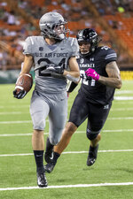 Air Force running back Kadin Remsberg (24) catches a pass and runs by Hawaii linebacker Solomon Matautia (27) for a touchdown during the first half of an NCAA college football game, Saturday, Oct. 19, 2019, in Honolulu. (AP Photo/Eugene Tanner)