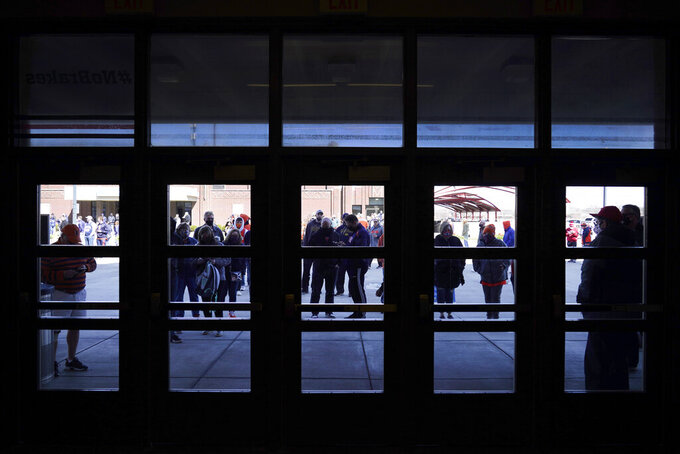 Basketball fans wait in silhouette outside the Indiana Farmers Coliseum before a first round NCAA college basketball game between Illinois and Drexel Friday, March 19, 2021, in Indianapolis. (AP Photo/Charles Rex Arbogast)