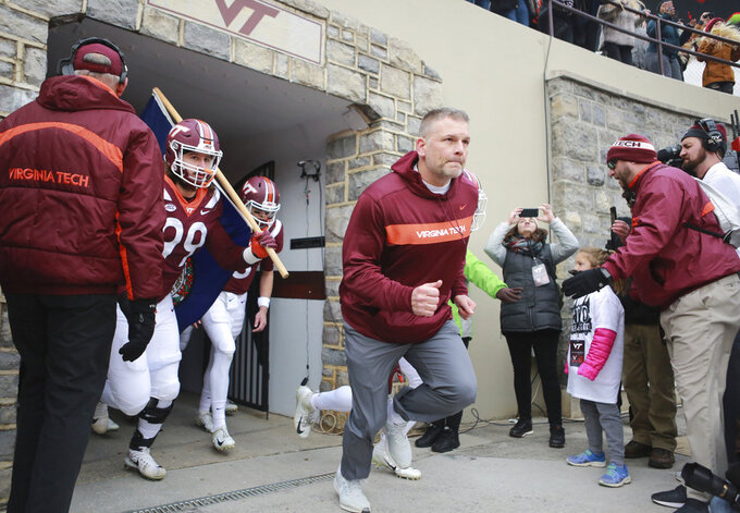 Virginia Tech head coach Justin Fuente leads his team onto the field at the start of an NCAA college football game against Virginia in Blacksburg, Va., Friday, Nov. 23, 2018. (Matt Gentry/The Roanoke Times via AP)