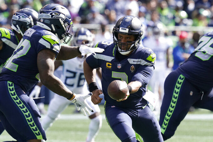 Seattle Seahawks quarterback Russell Wilson hands off to running back Chris Carson, left, during the first half of an NFL football game against the Tennessee Titans, Sunday, Sept. 19, 2021, in Seattle. (AP Photo/Elaine Thompson)