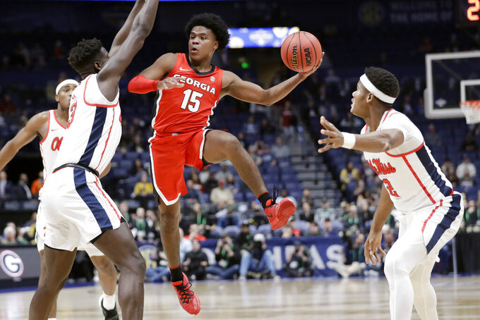 Georgia guard Sahvir Wheeler (15) drives between Mississippi defenders Khadim Sy (3) and Devontae Shuler (2) in the first half of an NCAA college basketball game in the Southeastern Conference Tournament Wednesday, March 11, 2020, in Nashville, Tenn. (AP Photo/Mark Humphrey)