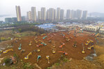 Heavy equipment works at a construction site for a field hospital in Wuhan in central China's Hubei Province, Friday, Jan. 24, 2020. China is swiftly building a 1,000-bed hospital dedicated to patients infected with a new virus that has killed 26 people, sickened hundreds and prompted unprecedented lockdowns of cities during the country's most important holiday. (Chinatopix via AP)