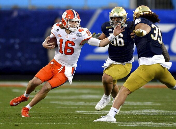 Clemson quarterback Trevor Lawrence, left, rushes against Notre Dame during the Atlantic Coast Conference championship NCAA college football game, Saturday, Dec. 19, 2020, in Charlotte, N.C. (Jeff Siner/The News & Observer via AP)