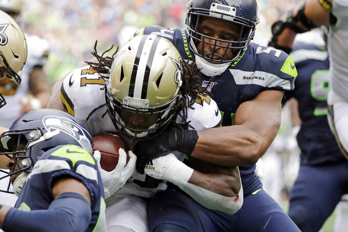 Seattle Seahawks' Bobby Wagner (54) tries to stop New Orleans Saints' Alvin Kamara on a carry during the second half of an NFL football game Sunday, Sept. 22, 2019, in Seattle. (AP Photo/Ted S. Warren)