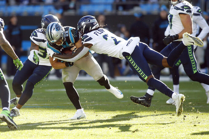 Seattle Seahawks cornerback Tre Flowers (21) defensive back Quandre Diggs tackle Carolina Panthers running back Christian McCaffrey (22) during the second half of an NFL football game in Charlotte, N.C., Sunday, Dec. 15, 2019. (AP Photo/Brian Blanco)