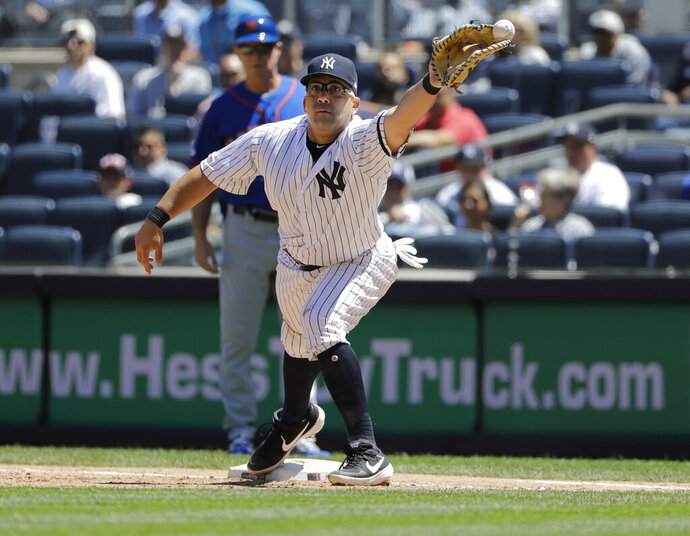New York Yankees first baseman Kendrys Morales can't field the throw allowing New York Mets' Todd Frazier to reach first base during the fourth inning in the first baseball game of a doubleheader, Tuesday, June 11, 2019, in New York. (AP Photo/Frank Franklin II)