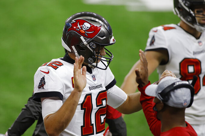 Tampa Bay Buccaneers quarterback Tom Brady (12) receives a high-five after a touchdown pass during the first half of an NFL football game against the Detroit Lions, Saturday, Dec. 26, 2020, in Detroit. (AP Photo/Al Goldis)