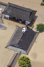 Residents are stranded on the rooftop of a house submerged in muddy waters that gushed out from the Kuma River in Hitoyoshi, Kumamoto prefecture, southwestern Japan, Saturday, July 4, 2020. Heavy rain triggered flooding and mudslides on Saturday, leaving more than a dozen missing. More than 75,000 residents in the prefectures of Kumamoto and Kagoshima were asked to evacuate following pounding rains overnight. (Kyodo News via AP)