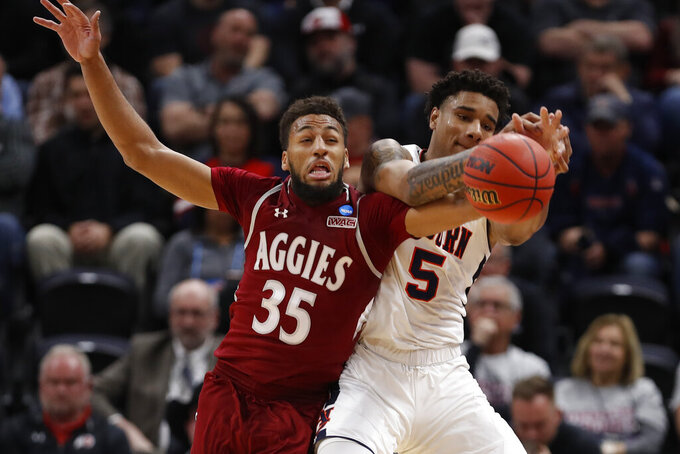 New Mexico State forward Johnny McCants (35) and Auburn forward Chuma Okeke (5) battle for the ball in the first half during a first round men's college basketball game in the NCAA Tournament Thursday, March 21, 2019, in Salt Lake City. (AP Photo/Jeff Swinger)