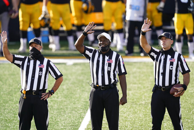 Officials wave to children in the University of Iowa Stead Family Children's Hospital at the end of the first quarter of an NCAA college football game between Iowa and Northwestern, Saturday, Oct. 31, 2020, in Iowa City, Iowa. (AP Photo/Charlie Neibergall)