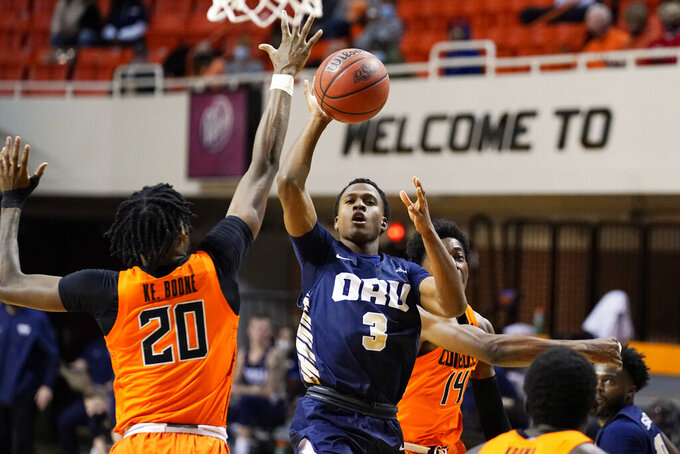 Oral Roberts guard Max Abmas (3) shoots between Oklahoma State guard Keylan Boone (20) and guard Bryce Williams (14) during the first half of an NCAA college basketball game Tuesday, Dec. 8, 2020, in Stillwater, Okla. (AP Photo/Sue Ogrocki)