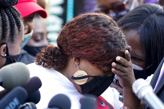 Tamika Palmer, the mother of Breonna Taylor, center, listens to a news conference, Friday, Sept. 25, 2020, in Louisville, Ky. Family attorney Ben Crump is calling for the Kentucky attorney general to release the transcripts from the grand jury that decided not to charge any of the officers involved in the Black woman's death. (AP Photo/Darron Cummings)