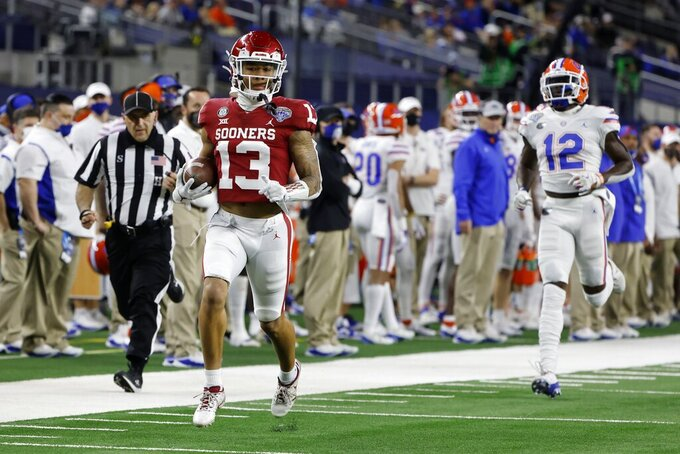 Oklahoma defensive back Tre Norwood (13) returns an interception for a touchdown as Florida wide receiver Rick Wells (12) gives chase during the first half of the Cotton Bowl NCAA college football game in Arlington, Texas, Wednesday, Dec. 30, 2020. (AP Photo/Michael Ainsworth)