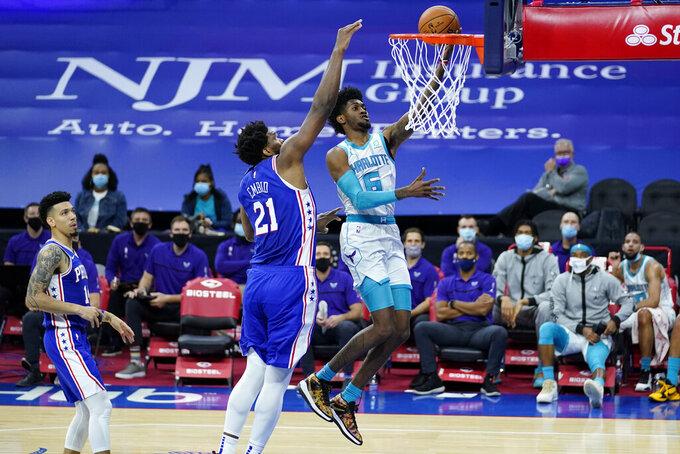 Charlotte Hornets' Jalen McDaniels (6) goes up for a shot past Philadelphia 76ers' Joel Embiid (21) during the first half of an NBA basketball game, Monday, Jan. 4, 2021, in Philadelphia. (AP Photo/Matt Slocum)
