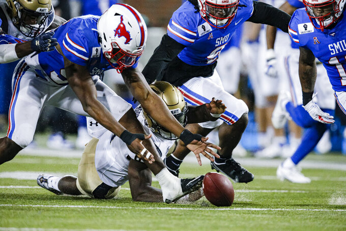 Navy quarterback Dalen Morris, center, fumbles the ball during the first half of an NCAA college football game, Saturday, Oct. 31, 2020, in Dallas. SMU defensive end Gary Wiley, left, recovered the ball. (AP Photo/Brandon Wade)