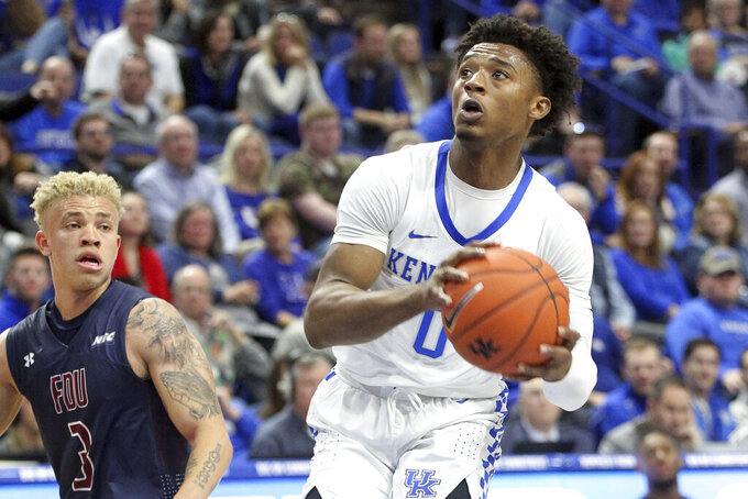 Kentucky's Ashton Hagans, right, looks for an opening near Fairleigh Dickinson's Jahlil Jenkins (3) during the first half of an NCAA college basketball game in Lexington, Ky., Saturday, Dec. 7, 2019. (AP Photo/James Crisp)