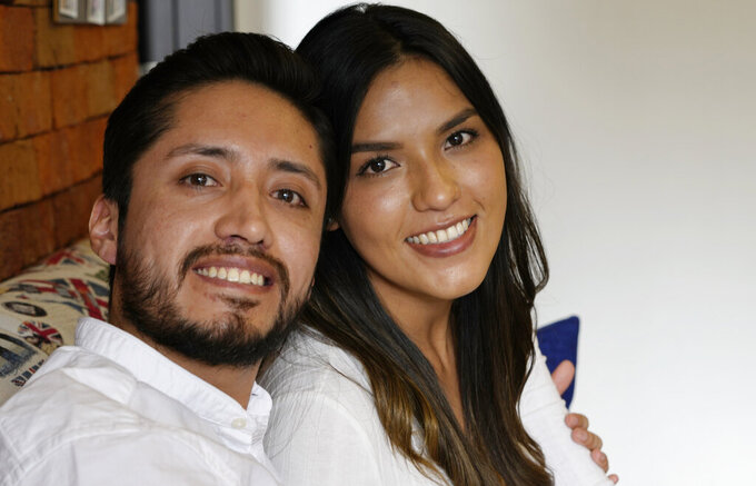 Doctor David Vallejo and his fiancee Doctor Mavelin Bonilla pose for a photo at home in Quito, Ecuador, Wednesday, June 9, 2021. Doctor Vallejo and Doctor Bonilla suspended their wedding in order to tend to COVID-19 patients and in the process Vallejo got sick himself with the disease, ending up in an ICU for several days. (AP Photo/Dolores Ochoa)