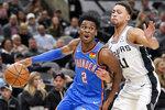 Oklahoma City Thunder's Shai Gilgeous-Alexander (2) drives against San Antonio Spurs' Bryn Forbes during the first half of an NBA basketball game, Thursday, Nov. 7, 2019, in San Antonio. (AP Photo/Darren Abate)