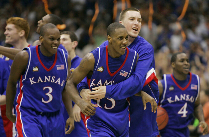 FILE - In this April 7, 2008, file photo, Kansas players Russell Robinson (3), Mario Chalmers (15) Brady Morningstar, rear, and Sherron Collins, right, celebrate their 75-68 victory over Memphis in the NCAA college basketball Final Four in San Antonio. (AP Photo/Eric Gay, File)