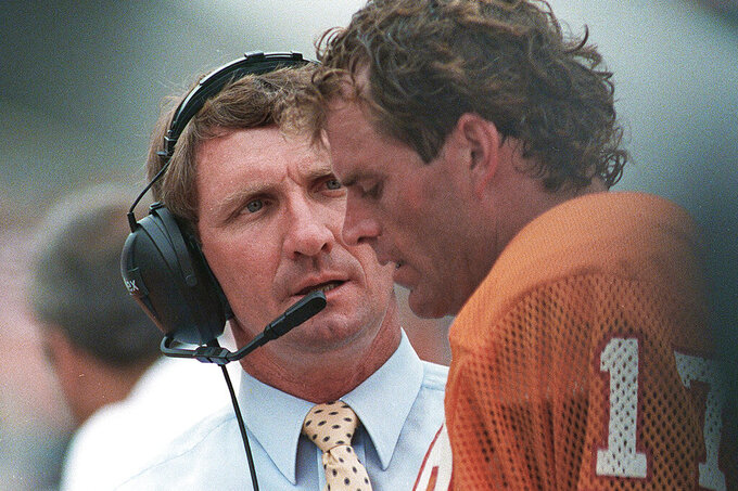 FILE - In this Sept. 13, 1987 file photo, Tampa Bay Buccaneers coach Ray Perkins, left, talks with quarterback Steve DeBerg on the sidelines during an NFL regular season opener against the Atlanta Falcons in Tampa, Fla. Perkins, who replaced Hall of Famer Bear Bryant as Alabama's football coach and started the transition with the New York Giants that led to two Super Bowl titles, died Wednesday morning, Dec. 9, 2020, in Tuscaloosa. He was 79. The school announced his passing on Wednesday, and daughter Rachael Perkins posted news of his death on her Facebook page. (AP photo/Kathy Willens, File)