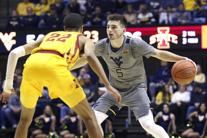 West Virginia guard Jordan McCabe (5) looks to pass the ball as he is defended by Iowa State guard Tyrese Haliburton (22) during the second half of an NCAA college basketball game Wednesday, Feb. 5, 2020, in Morgantown, W.Va. (AP Photo/Kathleen Batten)