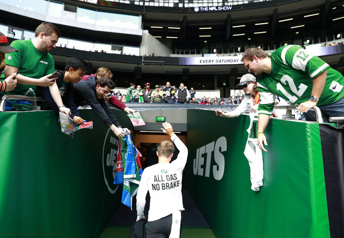 New York Jets quarterback Zach Wilson (2) leaves the field after the first warm-up before an NFL football game between the New York Jets and the Atlanta Falcons at the Tottenham Hotspur stadium in London, England, Sunday, Oct. 10, 2021. (AP Photo/Ian Walton)