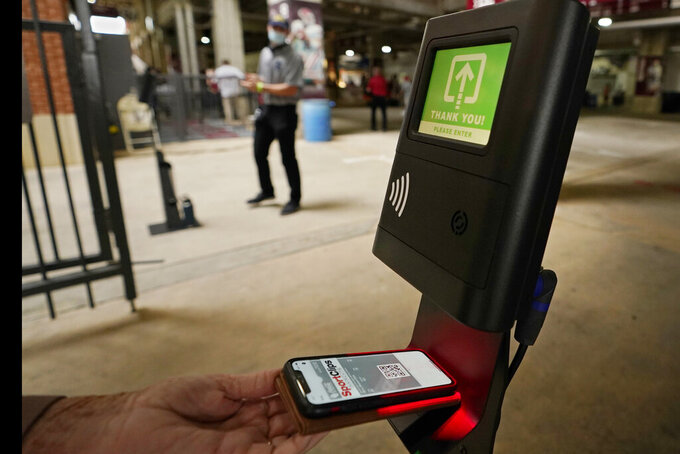 Fans use a touchless scanner for entrance to the Missouri State and  Oklahoma NCAA college football game Saturday, Sept. 12, 2020, in Norman, Okla. (AP Photo/Sue Ogrocki, Pool)