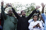 FILE - In this April 22, 2018, file photo, Manzoor Pashteen, center, a leader of Pashtun Protection Movement waves to his supporters during a rally in Lahore, Pakistan. Pakistan's police raided a home in the northwestern city of Peshawar before dawn Monday and arrested seven suspects, including Pashteen which has denounced alleged high-handedness of the military in former tribal regions. (AP Photo/K.M. Chaudary, File)
