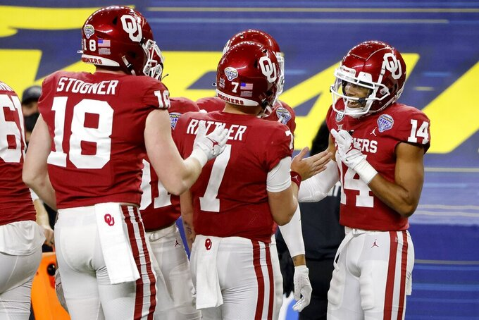Oklahoma tight end Austin Stogner (18), quarterback Spencer Rattler (7), wide receiver Charleston Rambo (14) and others celebrate a touchdown catch made by Rambo during the second half of the Cotton Bowl NCAA college football game against Florida in Arlington, Texas, Wednesday, Dec. 30, 2020. (AP Photo/Michael Ainsworth)