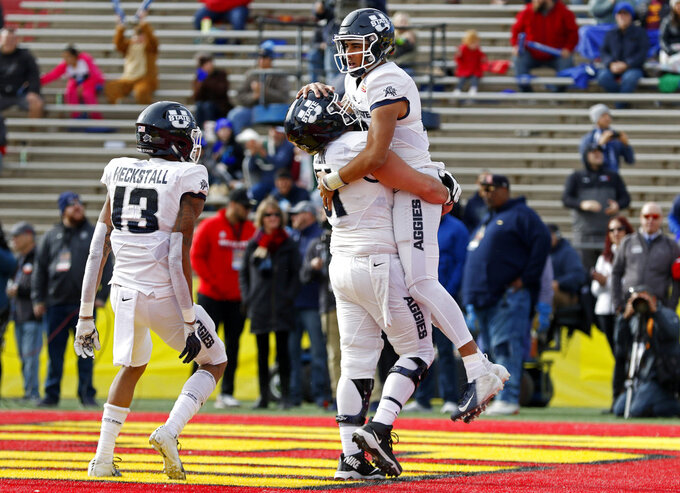 Utah State quarterback Jordan Love, right, celebrates with offensive lineman Quin Ficklin (51) after scoring a touchdown against North Texas during the first half of the New Mexico Bowl NCAA college football game in Albuquerque, N.M., Saturday, Dec. 15, 2018. (AP Photo/Andres Leighton)