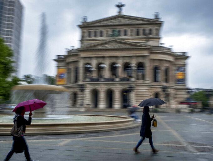 Women under umbrellas walk past the Old Opera in Frankfurt, Germany, during heavy rain fall on Thursday, June 4, 2020. (AP Photo/Michael Probst)