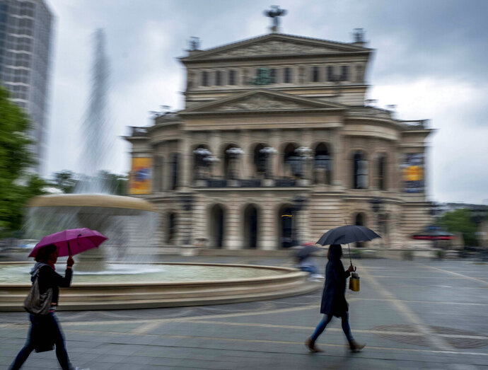 Women under umbrellas walk past the Old Opera in Frankfurt, Germany, during heavy rain fall on Thursday, June 4, 2020. (AP Photo/Michael Probst)