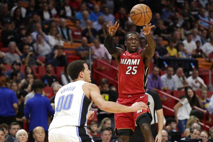 Miami Heat guard Kendrick Nunn (25) passes the ball past Orlando Magic forward Aaron Gordon (00) during the first half of an NBA basketball game Wednesday, March 4, 2020, in Miami. (AP Photo/Wilfredo Lee)