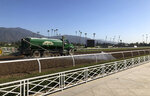 A truck waters the track at Santa Anita Park in Arcadia, Calif., Wednesday, Oct. 30, 3019. A tragic, wild and unusual year in horse racing culminates with the Breeders' Cup world championships this weekend at Santa Anita, where the fatalities have prompted investigations, outrage from the public, and animal rights activists demanding the end of racing in California. (AP Photo/Beth Harris)
