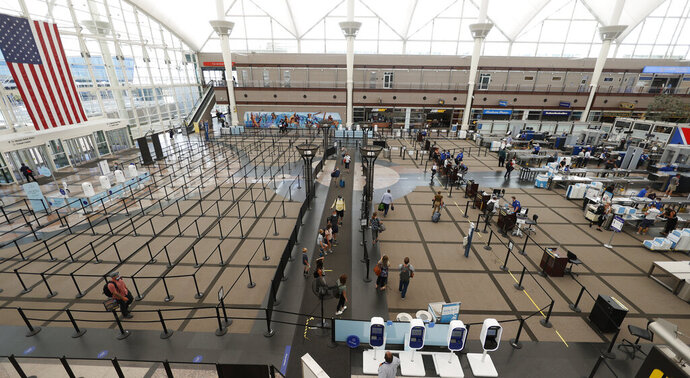 FILE - Travelers make their ways to the south security checkpoint in the main terminal of Denver International Airport Wednesday, July 22, 2020, in Denver.  U.S. public health officials are revising their travel advisory information. So if Taiwan or Greenland are in your travel plans, the Centers for Disease Control and Prevention says you can go ahead and pack your bags. Previously, the agency told U.S. travelers to avoid all nonessential travel because of the COVID-19 pandemic.  (AP Photo/David Zalubowski, File)