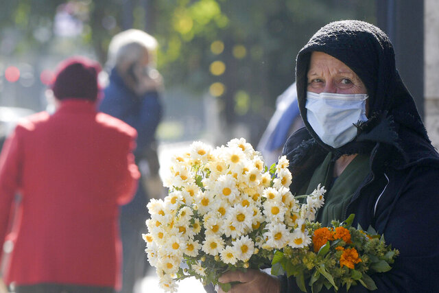 An elderly flower vendor wears a face mask for protection against COVID-19 infection in Bucharest, Tuesday, Oct. 20, 2020. Local authorities imposed the use of face masks in all public spaces, indoors and outdoors, closed schools, restaurants, theatres and cinemas after the rate of COVID-19 infections went above 3 cases per 1000 inhabitants in the Romanian capital Bucharest. (AP Photo/Andreea Alexandru)