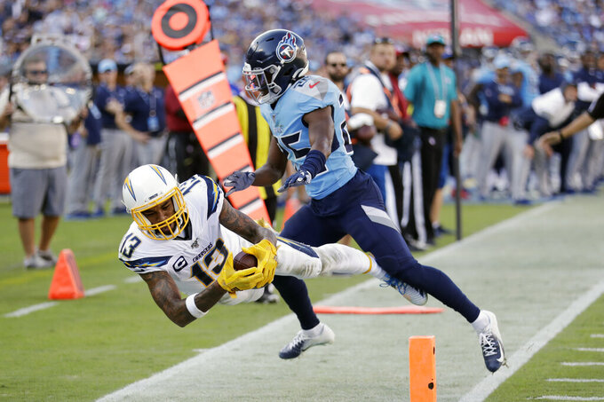 Los Angeles Chargers wide receiver Keenan Allen (13) hangs onto a pass as he falls out of bounds with Tennessee Titans cornerback Adoree' Jackson (25) in the first half of an NFL football game Sunday, Oct. 20, 2019, in Nashville, Tenn. (AP Photo/James Kenney)