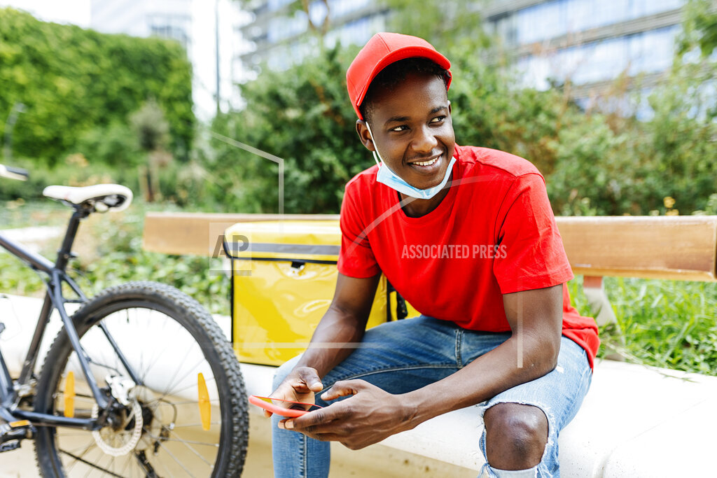 Smiling delivery man holding mobile phone while sitting on bench during pandemic