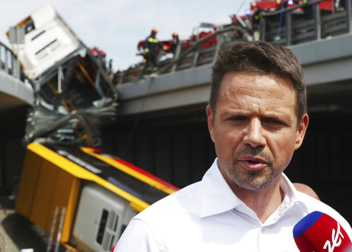 Warsaw Mayor Rafal Trzaskowski talking to reporters at the site of a city bus crash that killed one person and injured over 20 people when the articulate bus crashed off an overpass, in Warsaw, Poland, on June 25, 2020. Trzaskowski, who is a runner-up candidate in Sunday election for the nation's president, suspend his campaigning to come to the site.(AP Photo/Czarek Sokolowski)