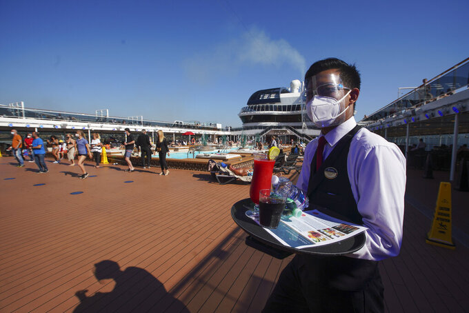 A waiter, wearing Covid-19 protection devices holds a tray of drinks on the MSC Grandiosa cruise ship in Civitavecchia, near Rome, Wednesday, March 31, 2021. MSC Grandiosa, the world's only cruise ship to be operating at the moment, left from Genoa on March 30 and stopped in Civitavecchia near Rome to pick up more passengers and then sail toward Naples, Cagliari, and Malta to be back in Genoa on April 6. For most of the winter, the MSC Grandiosa has been a lonely flag-bearer of the global cruise industry stalled by the pandemic, plying the Mediterranean Sea with seven-night cruises along Italy's western coast, its major islands and a stop in Malta. (AP Photo/Andrew Medichini)