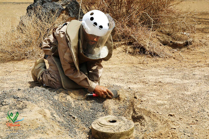 In this undated photograph released Aug. 19, 2018 by the state-run Emirates News Agency (WAM) on behalf of the Saudi-funded Masam anti-mine operation, an unidentified de-miner uncovers a mine near Marib, Yemen. Land mines scattered by Yemen's Houthi rebels will remain a threat even if the latest negotiations succeed in halting the civil war. While the Houthis' firing of ballistic missiles deep into Saudi Arabia has drawn the most attention, their widespread use of mines within Yemen represents a risk for generations to come in the Arab world's poorest country. Yemen is also littered with unexploded cluster munitions and bombs dropped by the Saudi-led coalition, including some made in the United States. (WAM via AP)