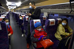 Passengers wearing face masks to protect against the spread of new coronavirus board the first high-speed train to leave Hankou train station after the resumption of train services in Wuhan in central China's Hubei Province, Wednesday, April 8, 2020. After 11 weeks of lockdown, the first train departed Wednesday morning from a re-opened Wuhan, the origin point for the coronavirus pandemic, as residents once again were allowed to travel in and out of the sprawling central Chinese city. (AP Photo/Ng Han Guan)