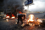 An anti-government protester burns tires, as they close the main highways during ongoing protests against the corruption and the Lebanese politicians, in Khaldeh, south of Beirut, Lebanon, Wednesday, Nov. 13, 2019. A local official for a Lebanese political party was shot dead by soldiers trying to open a road closed by protesters in southern Beirut late Tuesday, the army reported, marking the first death in 27 days of nationwide protests. (AP Photo/Hussein Malla)