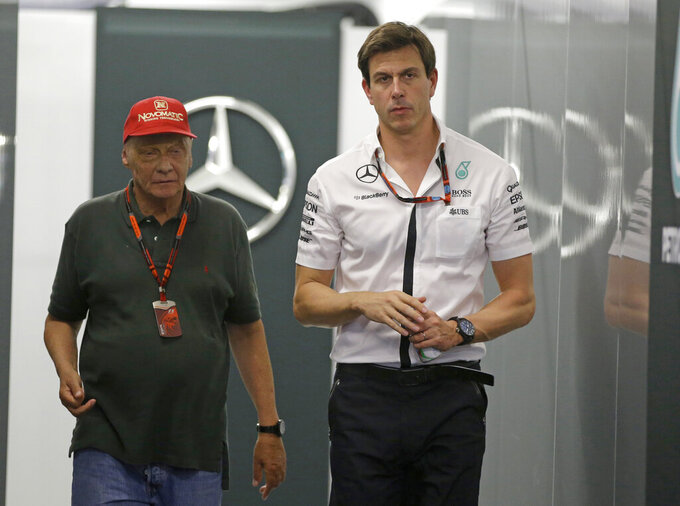 "FILE - In this Saturday, Sept. 19, 2015 file photo Head of Mercedes-benz Motorsports Toto Wolff, right, walks with former F1 champion Niki Lauda following the third practice session at the Singapore Formula One Grand Prix on the Marina Bay City Circuit in Singapore. Struggling to deal with his raw emotions, Mercedes head of motorsport Toto Wolff said losing his close friend Niki Lauda has left him feeling ""like a zombie"" and cast a ""huge black cloud"" of sadness over motorsport. (AP Photo/Mark Baker, File)"