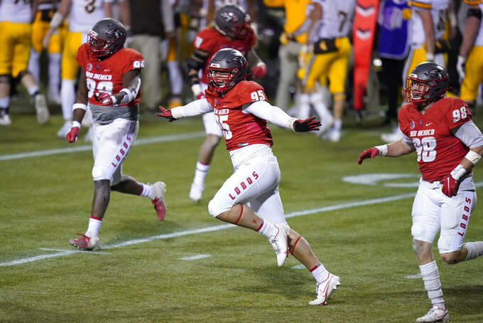 New Mexico defensive end Jake Saltonstall (95) celebrates with teammates after a play against Wyoming during the second half of an NCAA college football game Saturday, Dec. 5, 2020, in Las Vegas. (AP Photo/John Locher)