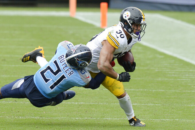 Pittsburgh Steelers running back James Conner (30) is hit by Tennessee Titans cornerback Malcolm Butler (21) in the first half of an NFL football game Sunday, Oct. 25, 2020, in Nashville, Tenn. (AP Photo/Mark Zaleski)