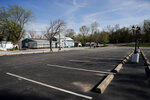 In this Tuesday, April 7, 2020 photo, a parking lot sits empty in Kimmswick, Mo. The tiny town along the banks of the Mississippi River, normally bustling with out-of-town visitors this time of year, is virtually empty as the economic ravages of the coronavirus has shuttered shops and restaurants in the community. (AP Photo/Jeff Roberson)
