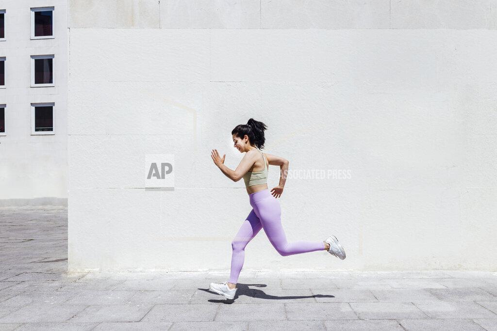 Sportswoman running on footpath